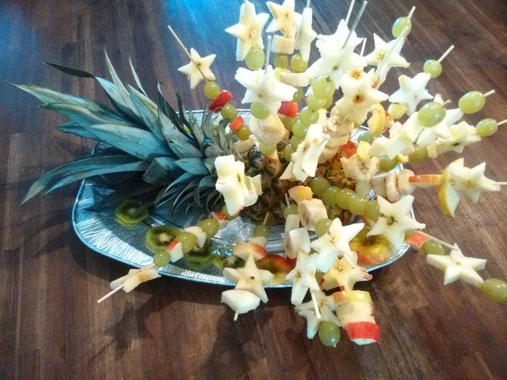 Fruitspiesjes voor kerstdiner op school. Sterren van appel, met druiven, banaan en ananas.