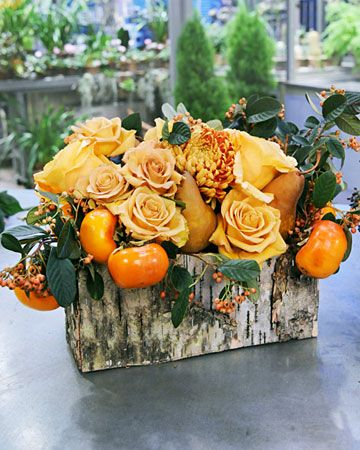 Staple birch bark to a pine box to create a rustic vessel for this arrangement. Use an assortment of flowers, foliage, and fruit to create a custom centerpiece.  (Or could use double sided tape to tape on the birch bark and then wrap around the vase a couple of times with wired twine.)