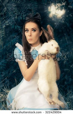 Funny Girl Costumed as Alice in Wonderland with The White Rabbit - Portrait of a surprised girl in a blue costume holding a white bunny