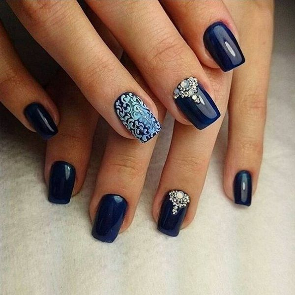 Elegant looking dark blue nail art design. You can see that there are tribal inspired designs that are added on top in white polish to make the design stand out more.