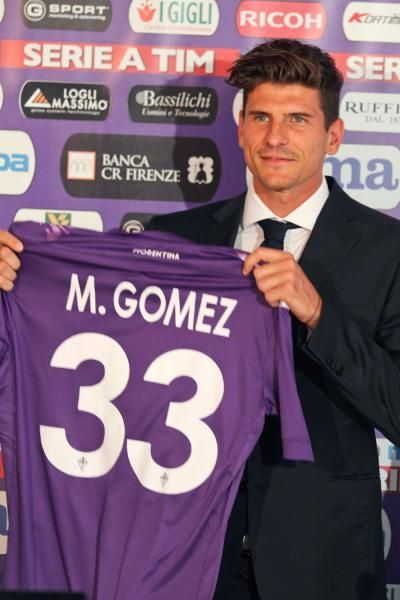 German striker Mario Gomez poses with his new jersey during his official presentation at the Artemio Franchi stadium in Florence, Italy, Monday, July 15, 2013. Gomez, who scored 112 goals in 172 games for Bayern across the past four seasons, transferred to Fiorentina for a reported transfer fee of Ä20 million ($26 million). (Matteo Bovo/Lapresse/AP)