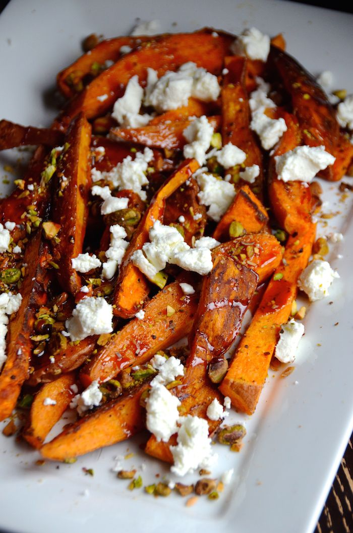Roasted sweet potato wedges are topped with crunch chopped pistachios, tangy goat cheese and a pomegranate glaze in this easy winter side dish recipe.