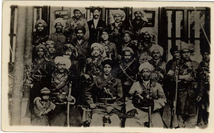 Photograph of  a group, seated and standing, of heavily armed men, said to be soldiers in the service of Bacha i Saqao (Habibullah Kalakani), dictator of Afghanistan in 1929.