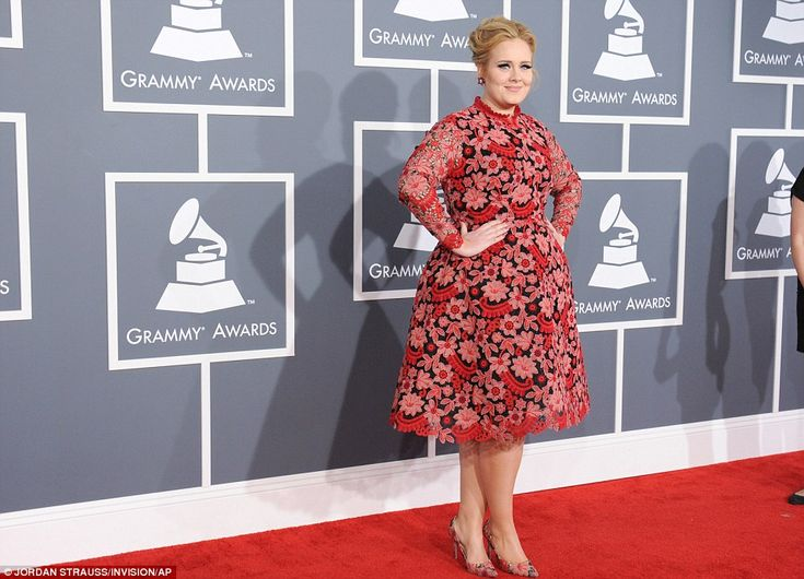 Coming up roses: Adele cut a striking sight in a knee length red and pink floral knee length dress and matching shoes