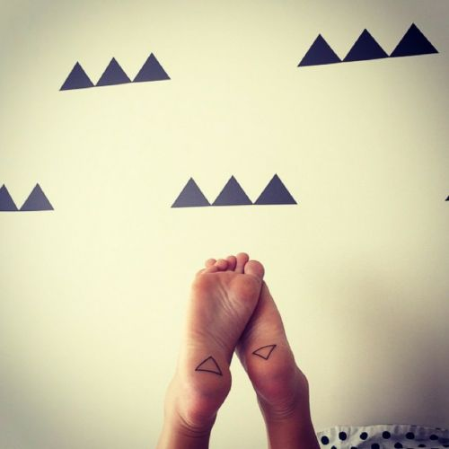 Little sole tattoo of two inversed triangles tattooed by Craigy Lee.