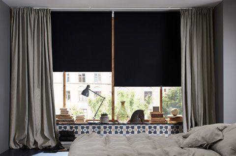 Ein Wohnzimmer mit großen Fenstern, u. a. eingerichtet mit TUPPLUR Verdunklungsrollos schwarz und dicken Gardinen in Grau.