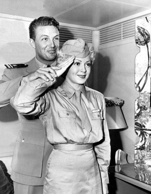 Navy Lieutenant Robert Stack teaches Lana Turner how to salute. October, 1944