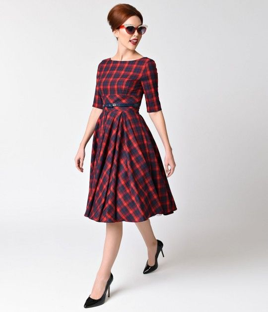 Made for a fabulous frolic! This delightful frock from The Pretty Dress Company in a gorgeous red and navy tartan plaid, cast in a classic retro dress design! Darling details include a chic high boat neckline which flows into a flattering back V, with h