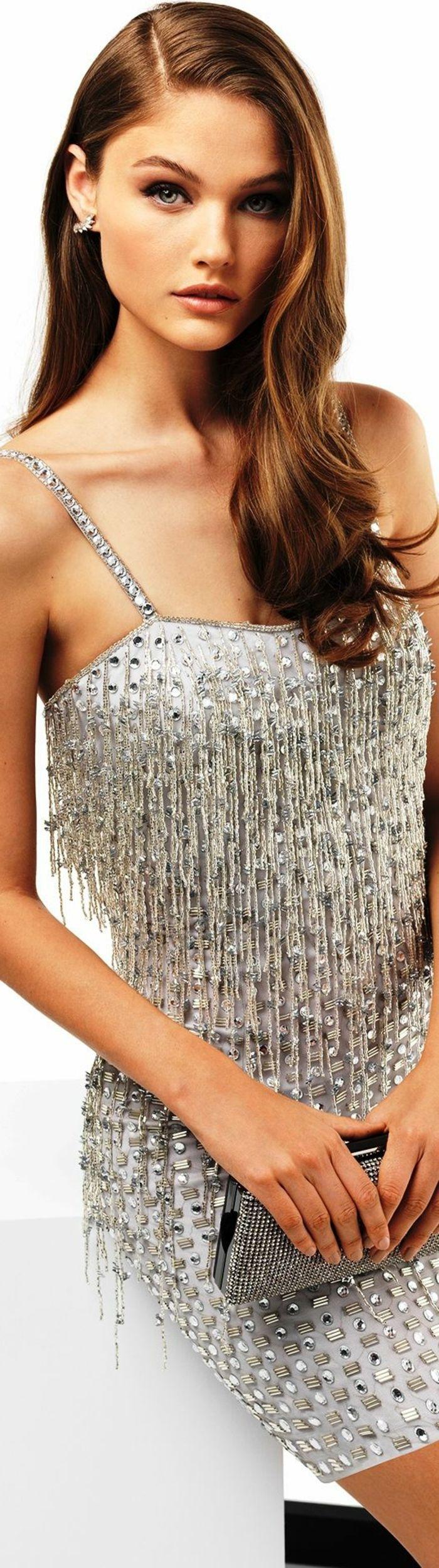 kurzes graues Cocktail-Kleid mit Kristallen und Troddeln, dünnen Trägern mit Kristallen und einem tiefen Ausschnitt, lange dunkelbraune Haare mit Seitenscheitel, graue Tasche ohne Henkel