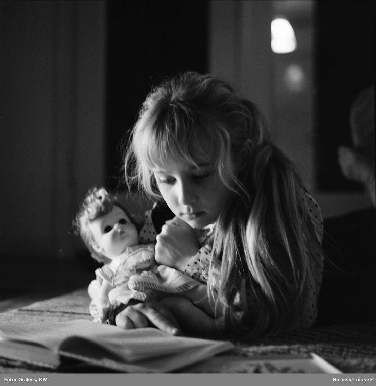 Flicka läser bok med docka i famnen. @ DigitaltMuseum.se