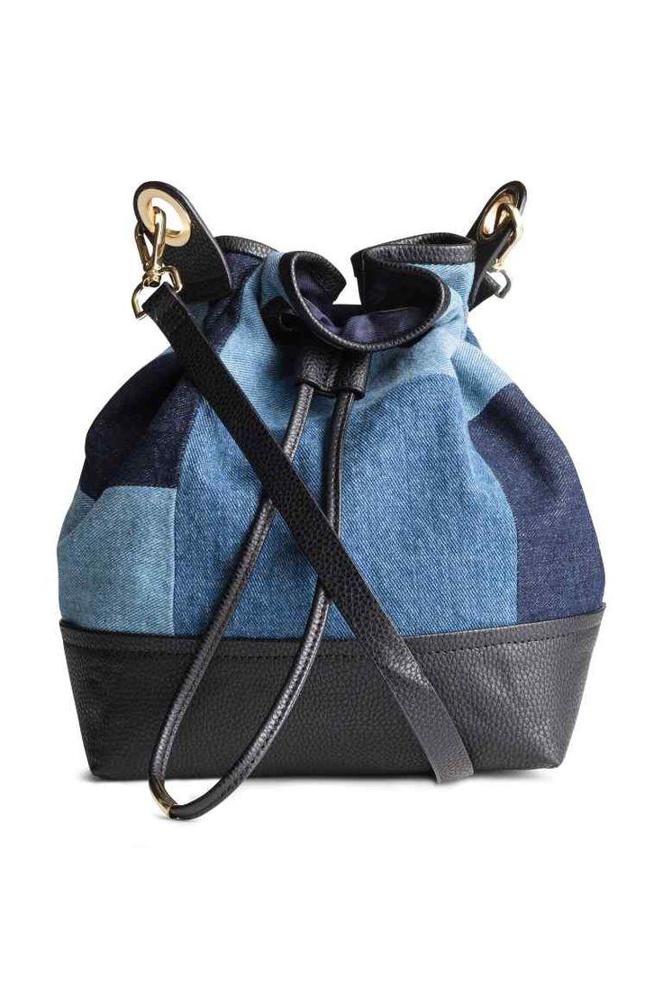 Sac seau en denim: Petit sac seau en denim et imitation cuir grené. Modèle avec lien de serrage en haut et fine bandoulière amovible. Une poche intérieure. Doublé. Dimensions 15,5x20,5x28 cm.