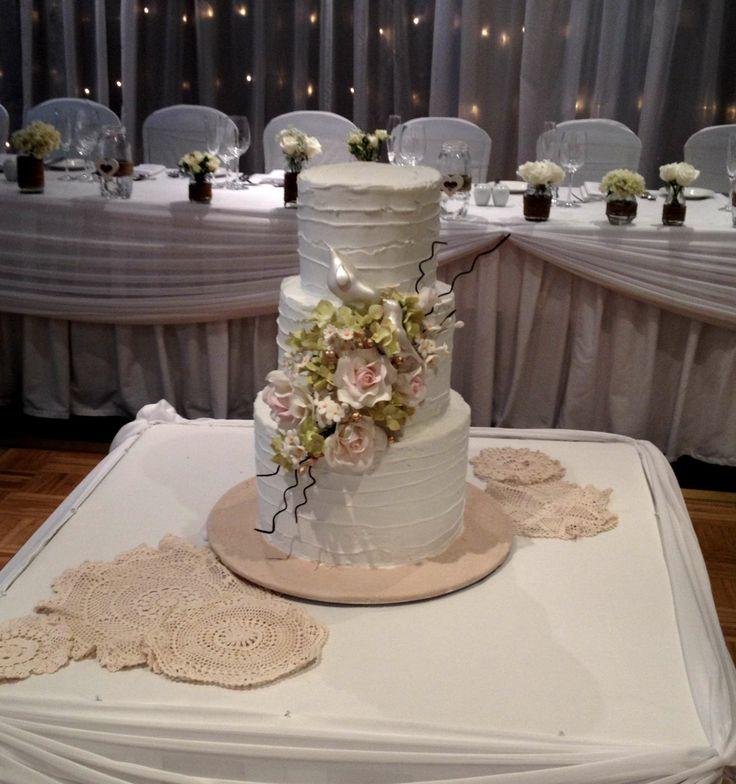 Sugar flowers and beautiful love birds adorn this buttercream cake.