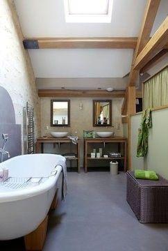 Une salle de bain sous les combles avec une très belle hauteur de plafond.