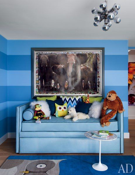 In Elton John and David Furnish's son Zachary's room, painted in stripes of Benjamin Moore blues, is outfitted with a vintage chrome chandelier from Downtown, a Martyn Lawrence Bullard-designed daybed, a Saarinen side table for Knoll from Design Within Reach, and a carpet by the Rug Company; the artwork is by Peter Beard.