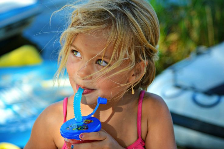 Beautiful child with blonde hair, green eyes and tanned skin.