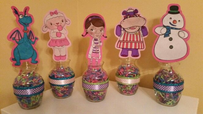 Doc McStuffins table centerpieces made from coloring book pages...cardstock...and dollar tree crinkle paper and vases :)