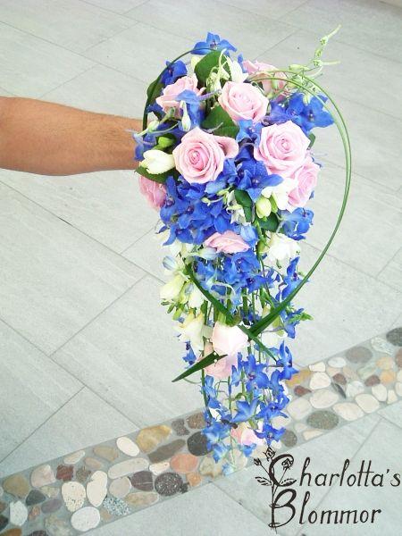 Brudbukett droppformad med rosa rosor,blå delphinium,vit fresia ,texasgräs och pärlnålar.