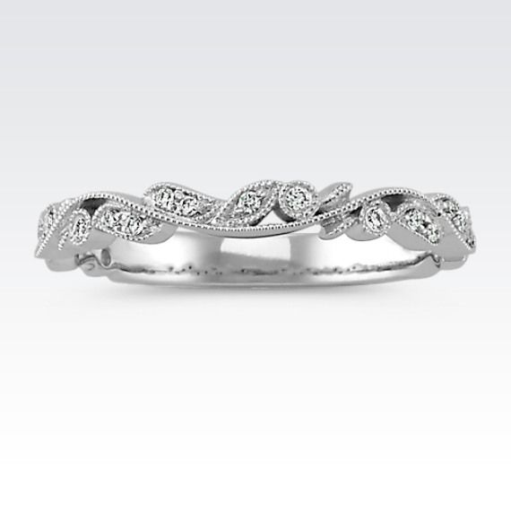 Add feminine, vintage-inspired design to your attire or to complement your existing engagement ring. This beautiful vintage wedding band features swirls of milgrain detailing accented by vine designs highlighted by a total of 16 round diamonds, at approximately .07 carat total weight. The ring measures 2.5mm wide.