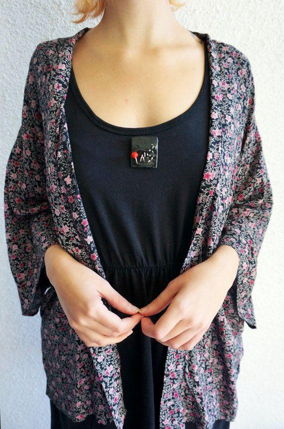 Spilla che è un piccolo quadro in miniatura, una tela nera con inserti di filo placcato argento che fioriscono in un piccolo tulipano stilizzato. 3,5 x