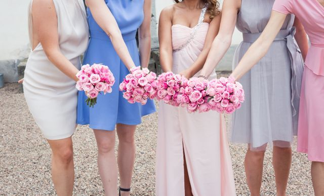 My bridesmaids with tone to tone dresses in pastel colours and their bouquets of pink peonies and roses.