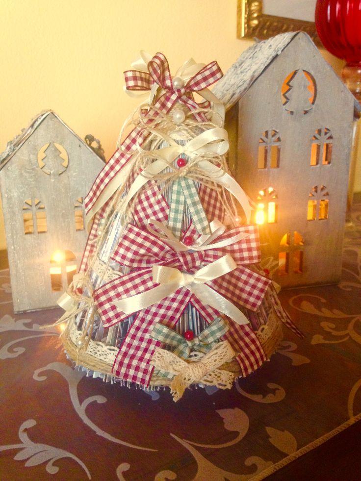 Albero di Natale realizzato con un catalogo di arredamento e addobbato con materiale riciclato.