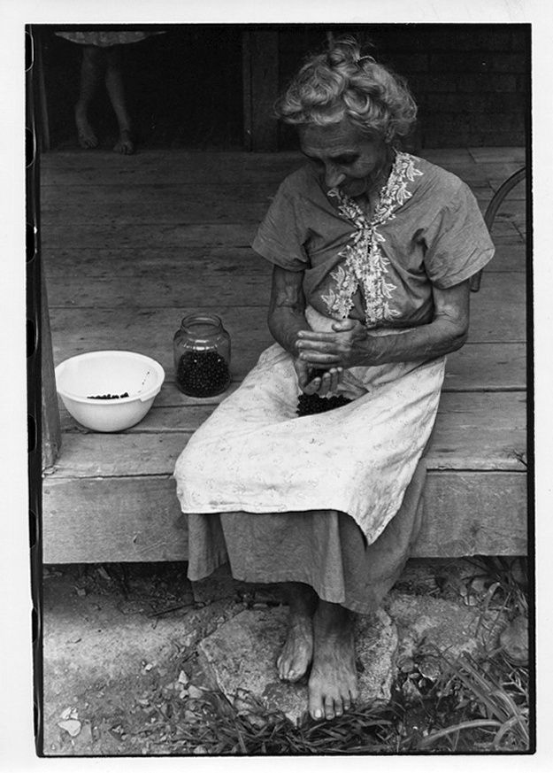 Elderly woman cleaning beans on a porch.. From Duke Digital Collections. Collection: William Gedney Photographs and Writings. Mark: Stamp. Date of print: Unknown.
