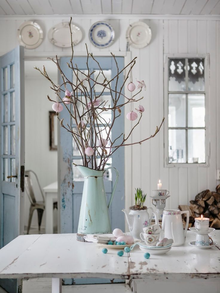 Love the softness of the white, blue doors. the random plates above the doors and the mirrored window makes the room reflect daylight