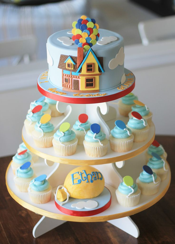 "Really loved making this cake.  Fondant covered top cake with hand cut ""Up"" house, clouds and balloons.  Coordinating cupcakes with fondant balloon toppers and buttercream balloon smash cake."