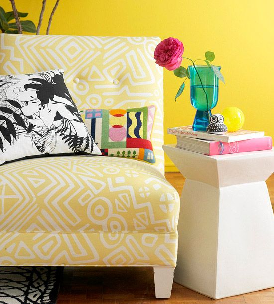 """""""When using strong colors, an accent wall goes a long way. Here, bicycle yellow makes a statement in the colorful living room. To ground and stabilize the use of bright colors, white was used on remaining walls and surfaces, such as the sofa and the dining room, kitchen, and coffee tables. It keeps occupants from feeling claustrophobic."""""""