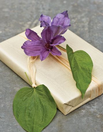 Here I wrapped a book in brown craft paper. Then I wrapped a piece of wet cotton ball around the stem of a clematis, and cover with floral tape. Tie it with raffia. The clematis will stay fresh for a few hours.