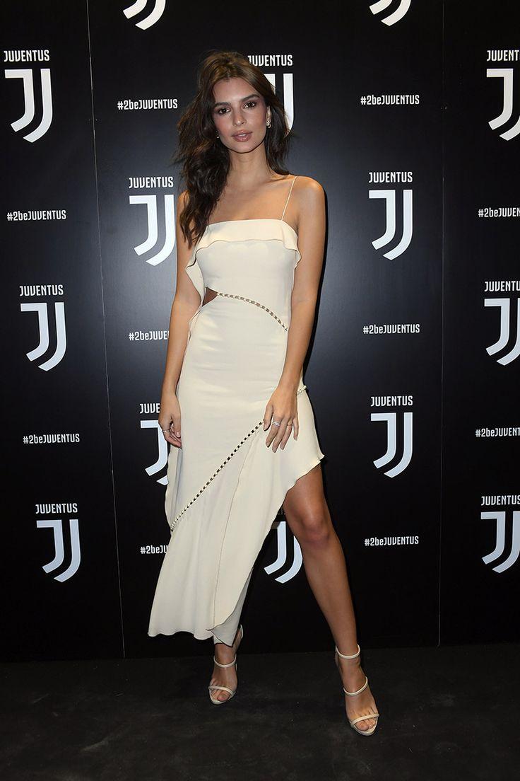 Emily Ratajkowski en la presentación del logo de la Juventus. Con vestido blanco con cut outs y bajo asimétrico, sandalias minimal blancas y pendientes de aro XS.
