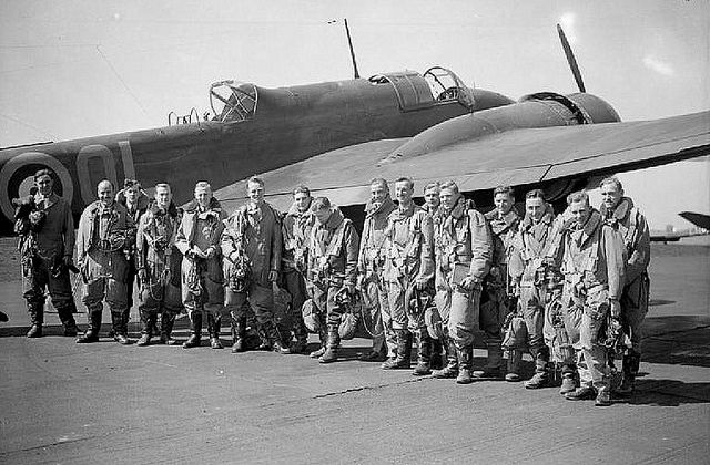 Bomber crews of No. 83 Squadron RAF line up by a Handley Page Hampden.
