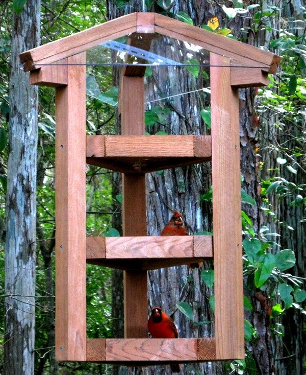These large bird feeders are beautifully handmade in the USA from select red cedar wood and see through plexiglass. These big decorative wood bird feeders have a fly through style that many songbirds prefer because they can see all around them while feeding and easily fly away in