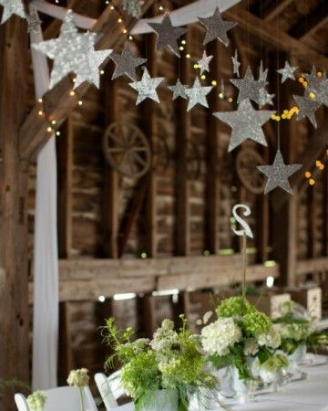 The bride recruited her sister to help her craft hundreds of silver stars from cardboard boxes and glitter. These hung above the rows of tables at the reception. The table numbers were made to match using leftover matte board and white glitter, and were mounted on sumac saplings plucked from the yard.