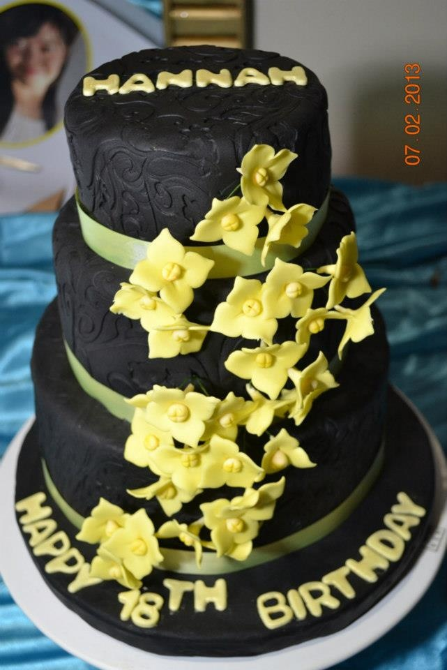Hannah's !8th Birthday cake, same as the debutante's motif, black and yellow. Chocolate cake covered with black fondant, decorated with yellow flowers and yellow ribbon.