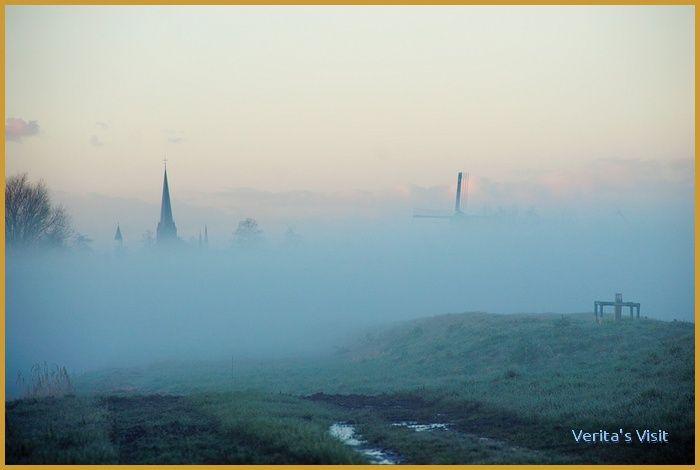 A Dutch #windmill & church in misty #polder landscape in winter. http://veritasvisit.nl