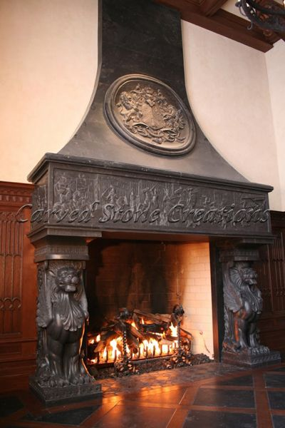 A unique custom Gothic fireplace by Carved Stone Creations. Artisan carvers incorporated a family crest into the overmantel and a large medieval scene relief carving that even included the homeowners riding on horseback to a jousting match.