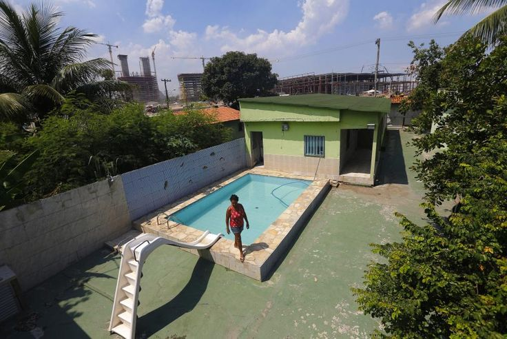 Marcias Lemos, 57, walks by a pool in her house, with cranes and construction work for the Rio 2016 Olympic Park seen in the background, at the Vila Autodromo favela in Rio de Janeiro January 28, 2015. REUTERS/Ricardo Moraes