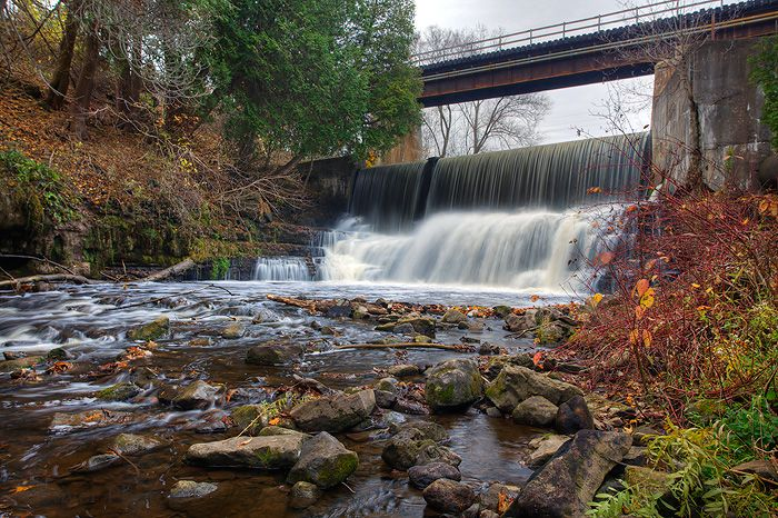 Progreston Falls: Ontario Waterfalls  From Highway 403 Hamilton, take Highway 6 north 11.5 km (7 miles) to Eighth Concession Rd. E. Proceed 2.8 km (1.6 miles) and take a left at Center Rd. After 0.9 km (0.5 miles), take a right on Progreston Rd and proceed 1.4 km (0.8 miles until the road takes a sharp bend by a railway bridge. The falls is under the bridge. Although there are a lot of man made structures around this falls, it still has charm.