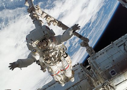 Anchored to the International Space Station's robot arm, STS-123 Mission Specialist Richard Linnehan participates in a spacewalk outside the orbital outpost. Photo credit: NASA