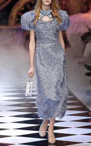 This **Dolce & Gabbana** dress features a scoop neck, a fitted bodice, voluminous short sleeves, and a tea length skirt.