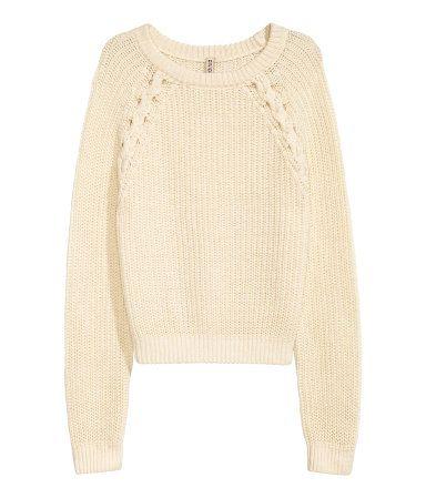 Gebroken wit. Een korte, grofgebreide trui van katoenmix met gevlochten details boven en raglanmouwen.