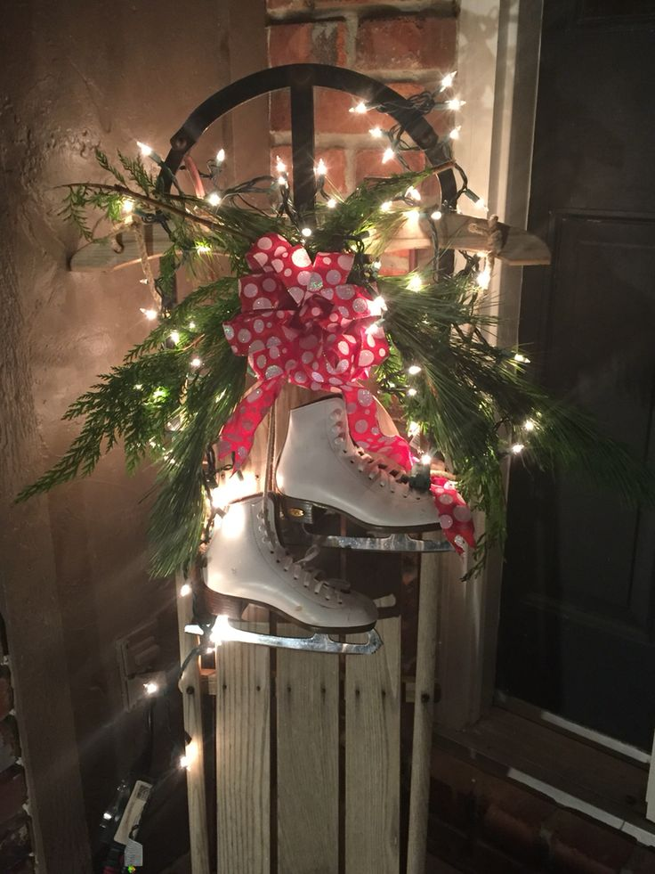 Old wooden sled decor made with fresh greenery, lights & children's ice skates