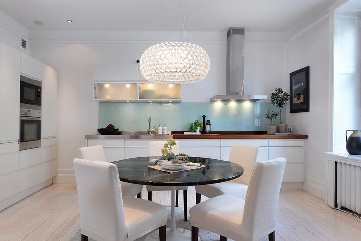 кухня белые гладкие фасады деревянная столешница подсветка обеденный стол кресла хрустальная люстра