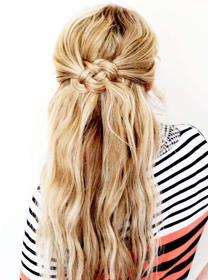 Such a cute half up half down twisted knotted bun hairstyle with loose waves