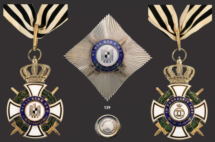 """ROMANIA: Order of the Royal House (1935). A Grand Officer's set military (1937): Neck Badge copper gilt both sides enameled blue enameled legend on obverse """"Nihil Sine Deo"""" and on reverse """"10 Februarie 1891"""" with original suspension ring loop and ribbon."""