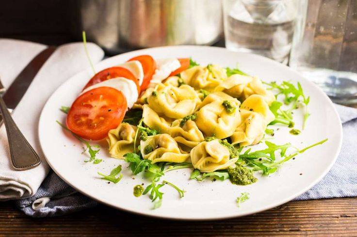 Recept voor verse pasta caprese voor 4 personen. Met zout, olijfolie, peper, verse pasta, groene pesto, rucola, mozzarella en tomaat