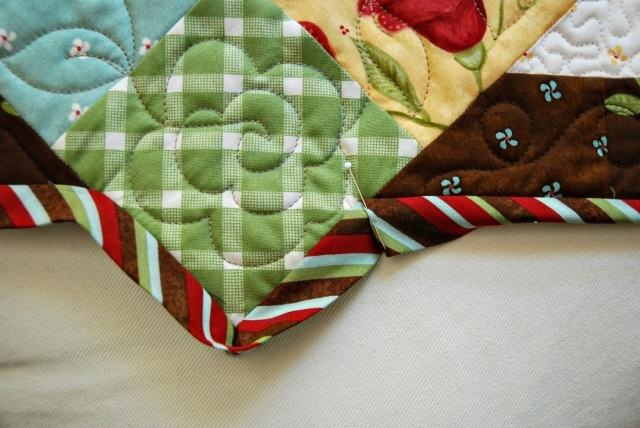 link is for binding an inside corner quilt tutorial but I love the freehand flower quilted in the corner
