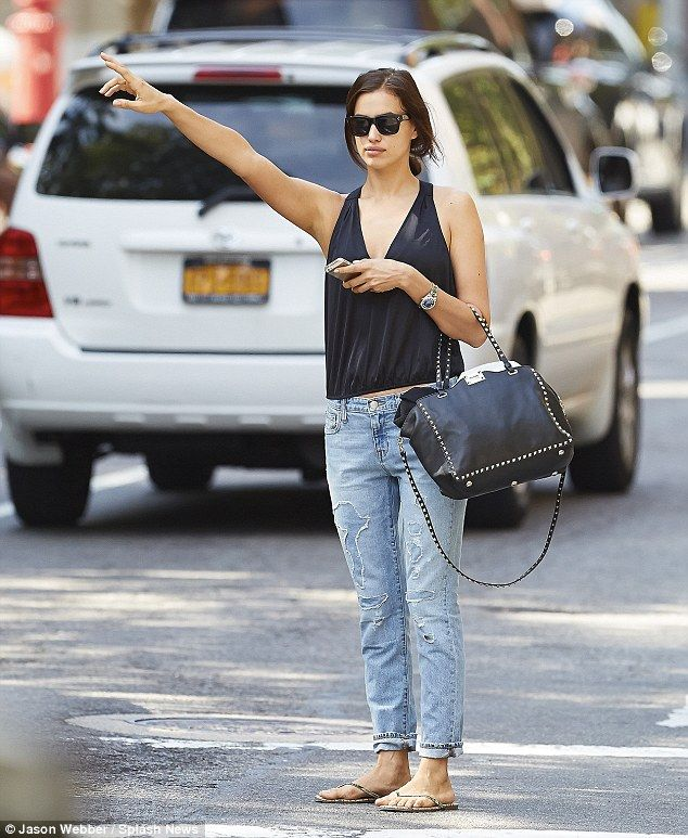 Irina Shayk hails a cab in New York's West Village wearing a loose top with ripped jeans and flip flops http://dailym.ai/1lx6woV