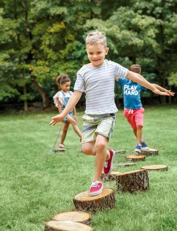 "Create this balance challenge with a path of cut logs in varying heights. Contact your local tree trimmer to see if he can donate scraps, or cut them yourself in heights ranging from 2"" to 10"". Space the stumps far enough apart so kids have to carefully plot each step as they walk the path."